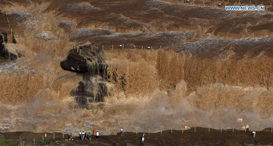 People watch scenery at Hukou Waterfall scenic spot in Shanxi