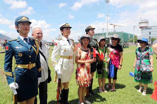 Civilians pose for photos with female service members during an event hosted by the People's Liberation Army Hong Kong Garrison on Monday. The two-day event, which began on Sunday, is part of celebrations marking Hong Kong's return 22 years ago. (Photo: China News Service/Hong Shaokui)