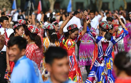 Nearly 10,000 residents dance in local Dolan Maxrap folk style in Awat county in the Xinjiang Uygur autonomous region on Oct 9, 2018. (Photo/China News Service)