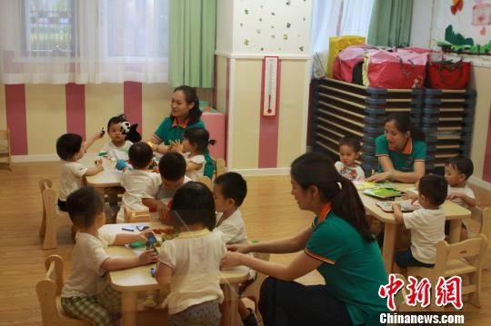 Teachers take care of children at a nursing center in Shanghai. (File photo/ China News Service)