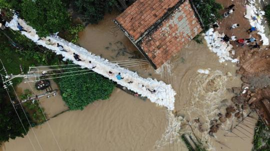Villagers and Armed Police officers distribute sandbags to contain floodwaters in Hengnan, Hunan province, on July 10, 2019. (ZHOU WEI/FOR CHINA DAILY)
