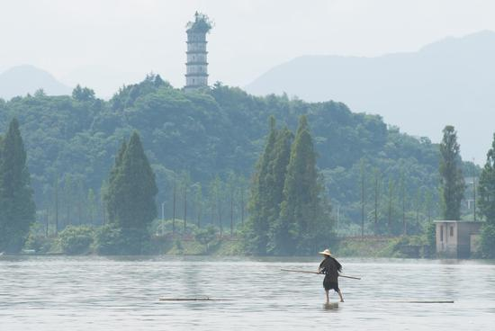 Fang Shuyun, 54, a native of Jiande City, crosses Xin'an River using two bamboo poles in Jiande City, east China's Zhejiang Province, July 11, 2019. Fang learned the trick when he was a kid. (Xinhua)