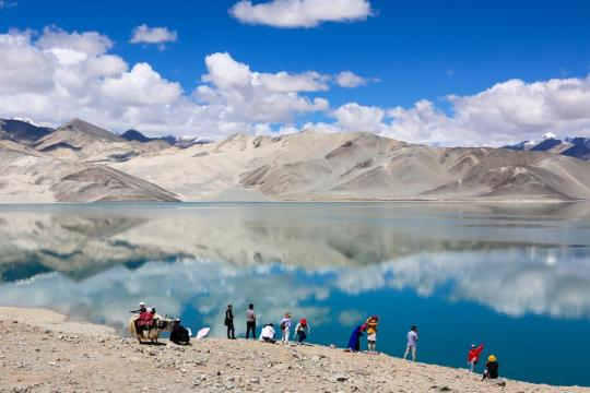 Tourists enjoy views of Baisha Lake, surrounded by snow-covered mountains on the Pamir Plateau in Akto county, Xinjiang Uygur autonomous region. (Photo/Xinhua)