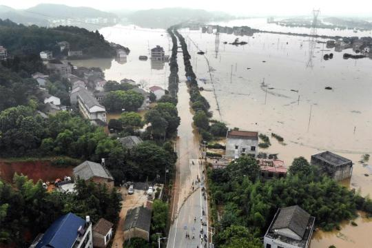 A main road leading to Hengdong county, Hunan province, was submerged by floodwaters on Thursday. The levee of a nearby river had two bursts of about 50 and 30 meters on Wednesday, leaving several villages soaked. (YANG HUAFENG/FOR CHINA DAILY)