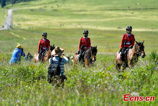 Horse riding guards add charm to grassland