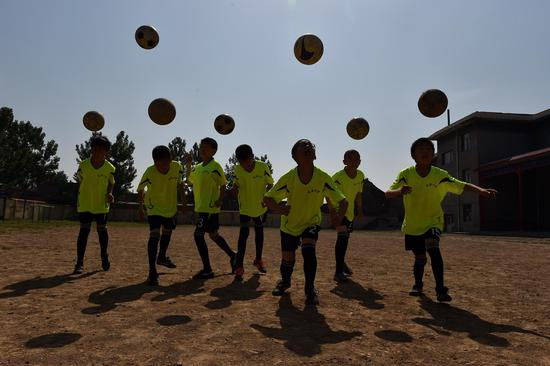 Students of Sima Primary School practise football in Xiaoyi City, north China's Shanxi Province, May 17, 2016. Many village schools have set up more sports courses during these years as they are encouraged to add more physical education classes if conditions permit. (Xinhua/Zhan Yan)