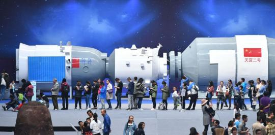 Visitors queue up to try out simulated games in front of a model of Tiangong-2 spacecraft at an aviation exhibition in Kunming, Yunnan Province. (Photo/China News Service)