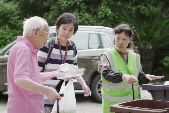 Zhou Chun (center) works with a local community worker to ensure the waste is correctly disposed of in Shanghai. (Photo/CHINA DAILY)
