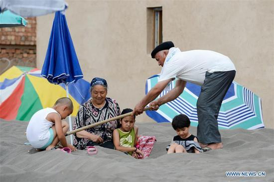 Sand therapy attracts tourists to NW China's Turpan