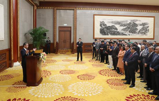 State Councilor and Foreign Minister Wang Yi (left) speaks at a gathering of Asian diplomats in Beijing, July 18, 2019. (Photo/Xinhua)