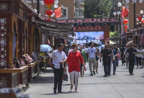 Tourists go sightseeing at the International Grand Bazaar in Urumqi, northwest China's Xinjiang Uygur Autonomous Region, July 13, 2019. The bazaar in Urumqi saw nearly 80,000 tourist trips per day during the recent tourist rush season. (Xinhua/Pan Ying)