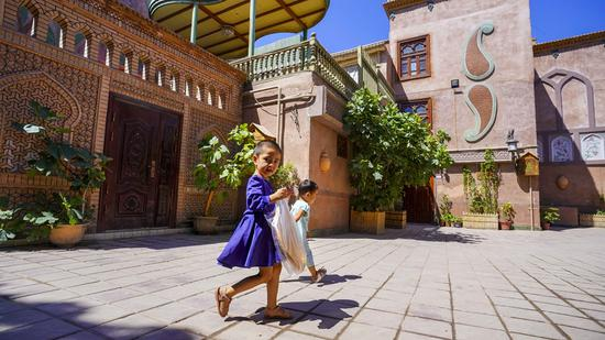 Children go home with Nang, a kind of crusty pancake, in the old town of Kashgar, northwest China's Xinjiang Uygur Autonomous Region, July 8, 2019. (Photo/Xinhua)