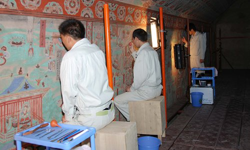Scientists repair the mural of Mogao Grottoes. (Photo/Courtesy of Dunhuang Academy)
