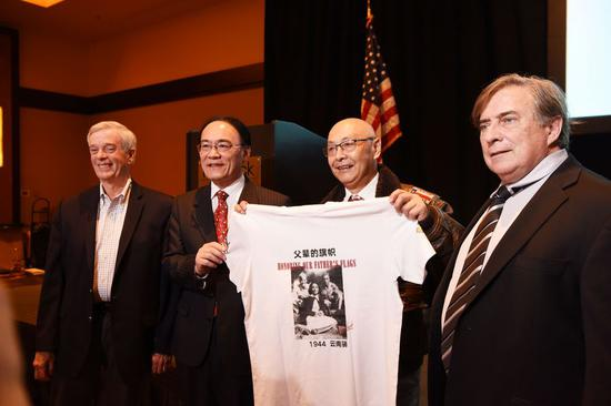 """Chinese Consul General in San Francisco Wang Donghua (2nd L), Jeffrey Greene (1st R), Chairman of the Sino-American Aviation Heritage Foundation, and other guests present a T-shirt with the forum theme of """"Honoring Our Father's Flags"""" at a Flying Tigers conference in Las Vegas, the United States, May 10, 2019. (Xinhua/Han Fang)"""