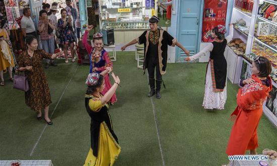 Tourists watch a performance staged by locals in the ancient city of Kashgar, northwest China's Xinjiang Uygur Autonomous Region, July 9, 2019. In the first half of 2019, the ancient city of Kashgar received over 310,000 tourists. (Xinhua/Zhao Ge)