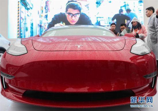 Visitors look at a Tesla Model 3 car in Shanghai, Jan. 7, 2019. (File photo/Xinhua)