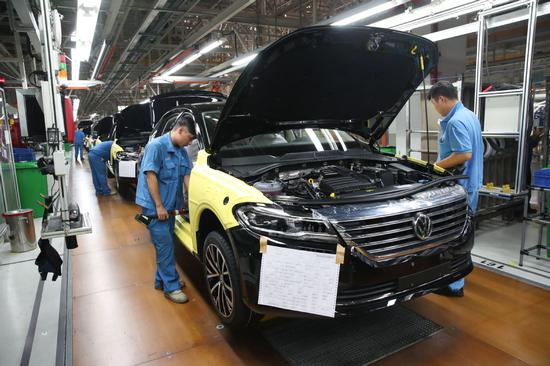 Employees put finishing touches to cars at the SAIC Volkswagen factory in Shanghai. [Photo/Xinhua]