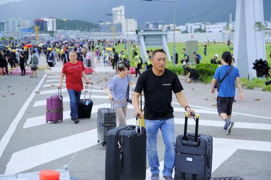 Passengers stride over barriers and walk to airport as radical protesters block the roads outside the Hong Kong International Airport in south China's Hong Kong, Sept. 1, 2019. (Xinhua)