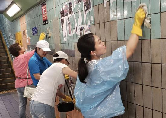 Volunteers scrub away posters in a tunnel in Hong Kong on Aug. 17. (Xinhua)