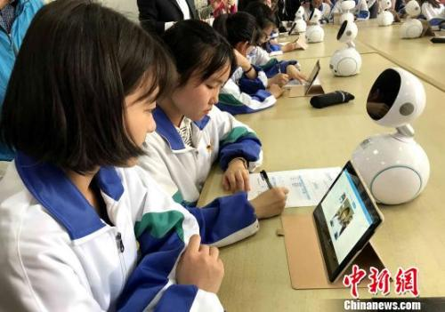 Students use a tablet PC to interact with a  robot in the classroom. (File photo/China News Service)