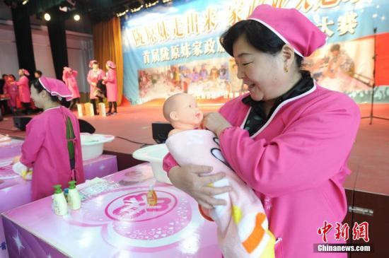 A home-service worker learns to take care of a baby at a domestic company in Gansu. (File photo/China News Service)