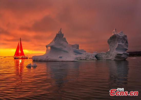 Beautiful red sailboat next to a massive iceberg