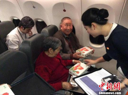 An airline stewardess distributes food on a passenger plane. (File photo/China News Service)