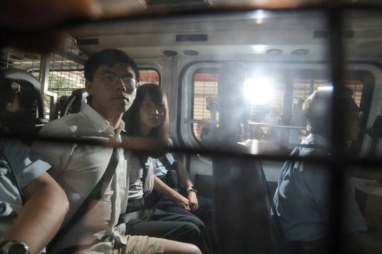 oshua Wong Chi-fung and Agnes Chow Ting are escorted in a police vehicle to the Eastern Magistrates' Court for a court appearance on the afternoon of Aug 30, 2019, after they were arrested in the morning the same day. (Photo/China Daily)