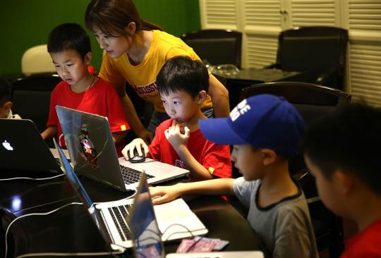 A teacher explains how to use coding to create games at a summer camp organized by Codemao, an education group, in Beijing in July, 2018. (Photo by Zou Hong/China Daily)