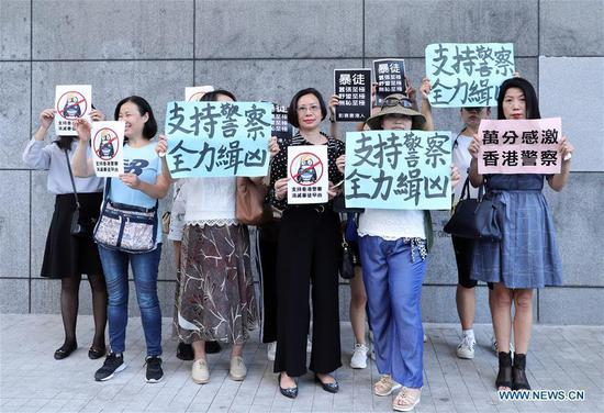 Citizens hold banners in support of police officers outside Hong Kong Police HQ