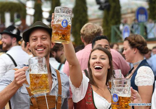 People drink beer in a festival tent during the first day of the Oktoberfest 2019 in Munich, Germany, Sept. 21, 2019. The 186th Oktoberfest, one of the world's largest folk festivals, officially opened here on Saturday. It is expected that around 6 million visitors from all over the world will enjoy festival beer and culinary delicacies here from Sept. 21 to Oct. 6. (Xinhua/Lu Yang)