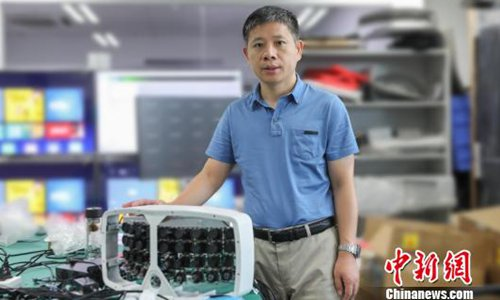 Zeng Xiaoyang pose for a picture with the artificial intelligence (AI)-enabling 500 megapixel cloud camera device. (Photo/China News Service)