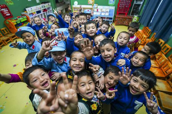 Children pose for a photo at a kindergarten at Liangzhongchang Village in Yutian County of Hotan, northwest China's Xinjiang Uygur Autonomous Region, Feb. 13, 2019. (Xinhua/Zhao Ge)