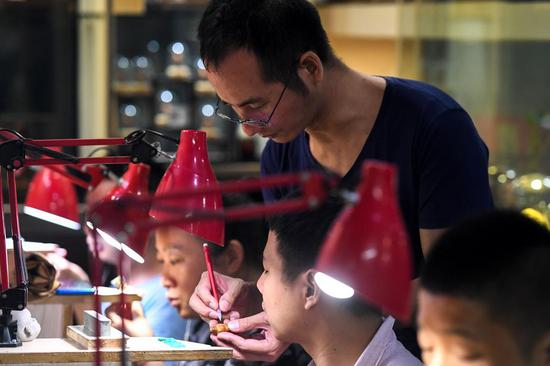 A craftsman (Up) teaches his apprentices fruit pit carving skills in Changsha, central China's Hunan Province, Sept. 18, 2019. (Xinhua/Chen Zeguo)