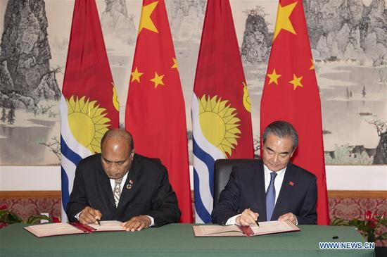 Chinese State Councilor and Foreign Minister Wang Yi (R) and Kiribati's President Taneti Mamau sign documents to restore diplomatic relations between the two countries at the Chinese Permanent Mission to the United Nations in New York, on Sept. 27, 2019. (Xinhua/Liu Jie)