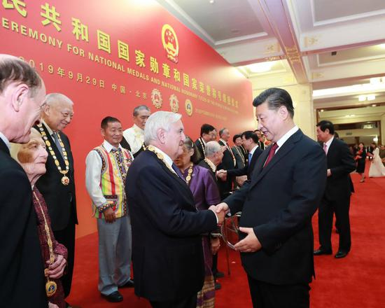 Chinese President Xi Jinping, also general secretary of the Communist Party of China Central Committee and chairman of the Central Military Commission, communicates with Jean-Pierre Raffarin, the honoree of the Friendship Medal, at the Great Hall of the People in Beijing, capital of China, Sept. 29, 2019. (Xinhua/Pang Xinglei)