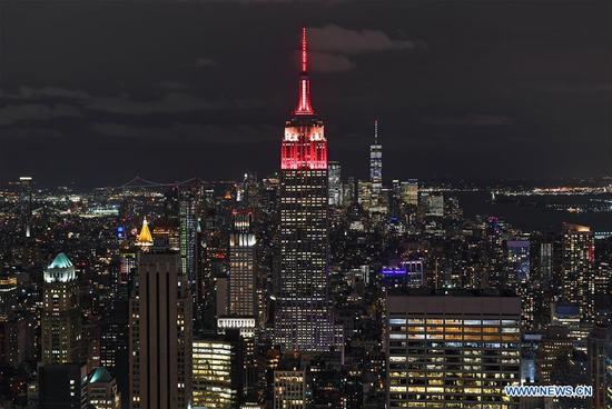 The top of the New York City's landmark Empire State Building (C) is lit up red and yellow in celebration of the 70th anniversary of the founding of the People's Republic of China (PRC) in New York City, the United States, on Sept. 30, 2019. New York City's landmark Empire State Building was lit with a light show on Monday night in celebration of the 70th anniversary of the founding of the People's Republic of China (PRC). The tower lighting also marks the 40th anniversary of the establishment of diplomatic relations between the United States and the PRC. (Xinhua/Li Rui)