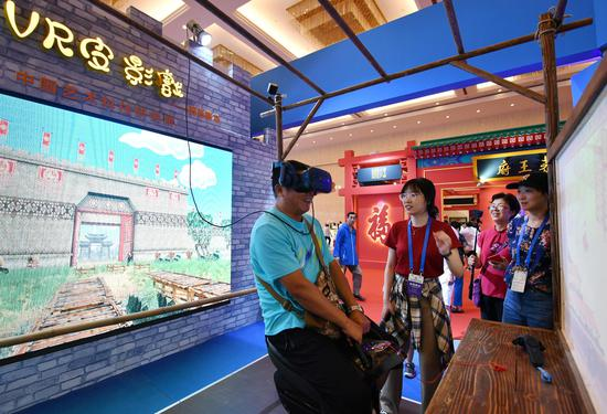 One visitor was using VR gear to watch a shadow play during the China Tourism Industry Expo held in Tianjin between Sept 6-8. (Xinhua/Mao Zhenhua)