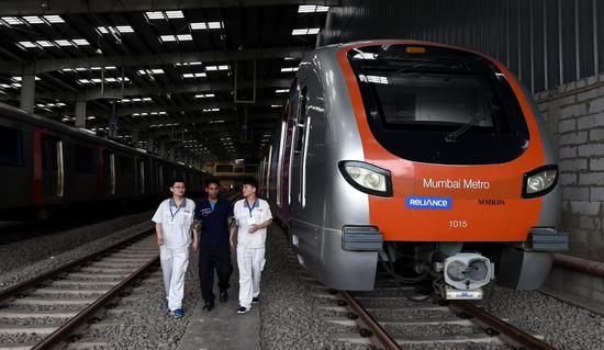 Chinese and Indian staff work at a metro car depot of Metro Line 1, in Mumbai, India, on June 27, 2018. Mumbai Metro Line 1 became operational on June 8, 2014, with its trains produced by China's CRRC Nanjing Puzhen Co., Ltd. (Xinhua/Zhang Naijie)