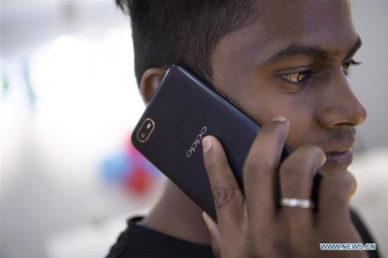 A man uses a phone with Chinese Oppo brand at a shopping mall in Chennai, India, Oct. 8, 2019. Film, yoga, smartphone industries enhance China-India links (Xinhua/Lui Siu Wai)