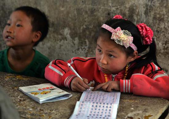 A girl attends a class at a rural school in Bijie, Guizhou province. [Photo by Peng Nian/For China Daily]