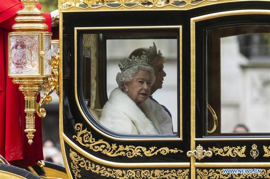 British Queen Elizabeth II travels by carriage along The Mall ahead of the State Opening of Parliament ceremony at the Palace of Westminster in London, Britain, Oct. 14, 2019. British Queen Elizabeth II opened a new session of the British parliament Monday in a ceremony packed with pomp and ceremony. (Photo by Ray Tang/Xinhua)