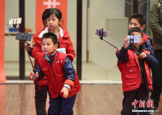Children experience live-streaming at a sci-tech cultural event, Jan. 20, 2018. (File photo/China News Service)