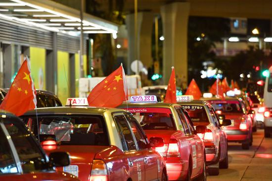 Taxis hanging Chinese national flags participate in a peace rally in Hong Kong on Aug. 23, 2019. Tse Ting-cheung also participated in the rally. (Xinhua)