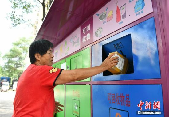 A resident puts garbage into a trash can in Beijing. (File photo/China News Service)