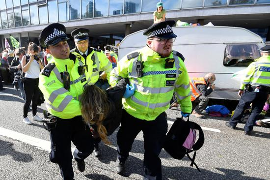 Police officers carry away an activist as Extinction Rebellion protesters block a road with caravan in central London, Britain, October 15, 2019.  (Photo/Agencies)