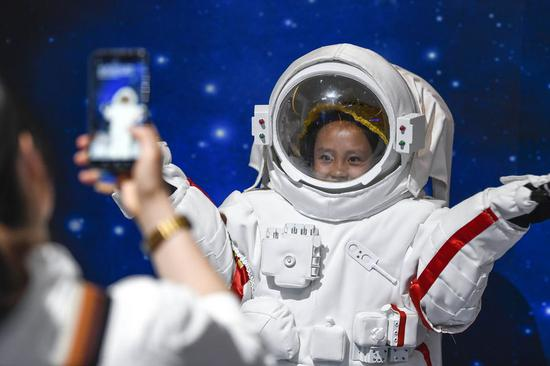 A young visitor poses for photos in a space suit during a juvenile science festival in Yinchuan, northwest China's Ningxia Hui Autonomous Region, Sept. 21, 2019. (Xinhua/Feng Kaihua)
