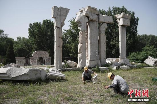 Staff members clean up weeds at ruins of Yuanying Guan (Immense Ocean Observatory) at Yuanmingyuan in Beijing, capital of China, May 23, 2018.  (Photo/China News Service)
