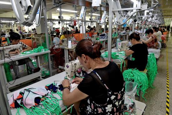 Workers sew swimsuits at a factory of the Qicaihu Garments & Weaving Co., Ltd. in Jinjiang, southeast China's Fujian Province, Aug. 14, 2019. (Xinhua/Zhang Guojun)