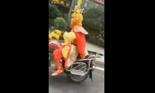 Mere mortal motorcycling Monkey King forgets his helmet